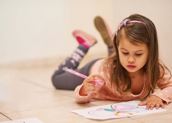 A child coloring on the floor