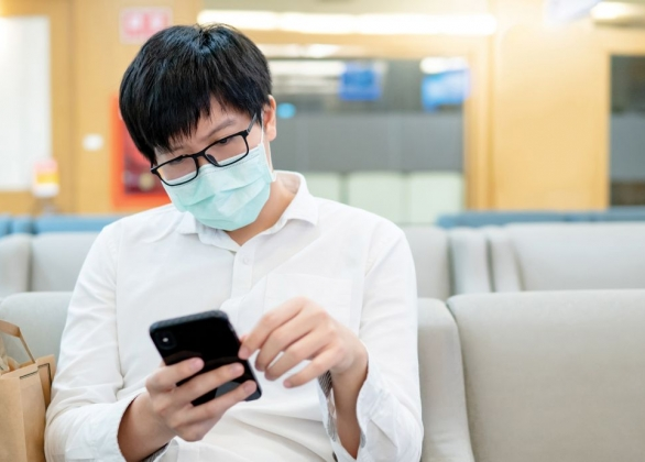 Man wearing a mask using his phone
